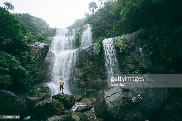 Man with jungle waterfall in Iriomote Island National Park, Japan
