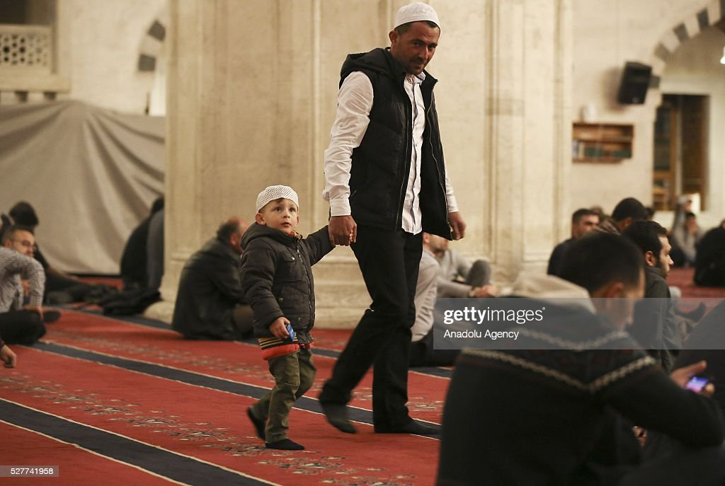 A man with kid attends a ceremony to mark the Islamic event of Miraj Night or Lailat al Miraj at Kocatepe Mosque in Ankara, Turkey on May 3, 2016.