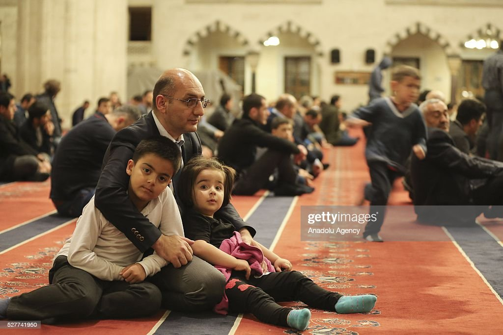 A man with kids attends a ceremony to mark the Islamic event of Miraj Night or Lailat al Miraj at Kocatepe Mosque in Ankara, Turkey on May 3, 2016.