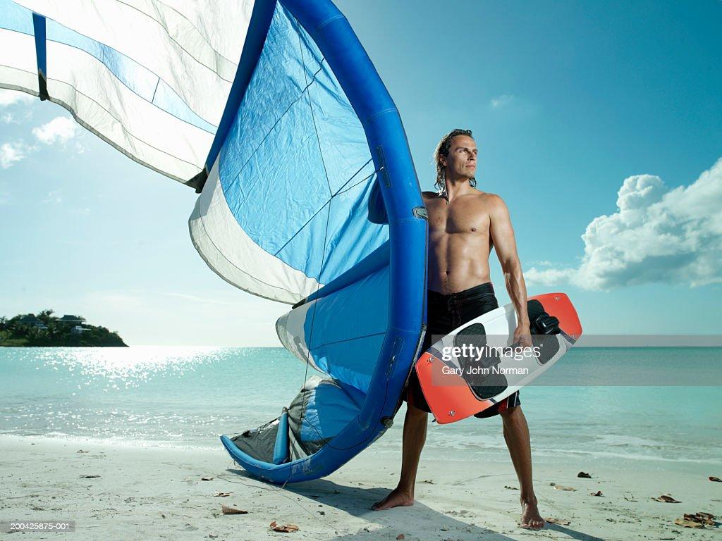 Man with kite-surfing gear on beach