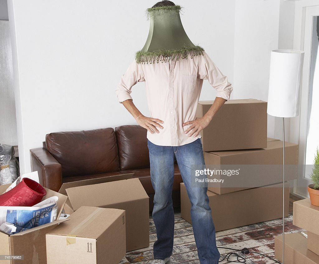 Man with lamp shade on head in home with cardboard boxes : Stock Photo