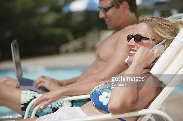 Man with laptop and woman talking on cell phone by pool