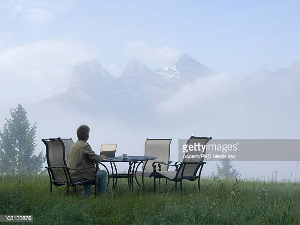 Man with laptop computer in misty mountain meadow