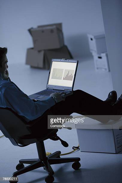 Man with laptop in room with boxes