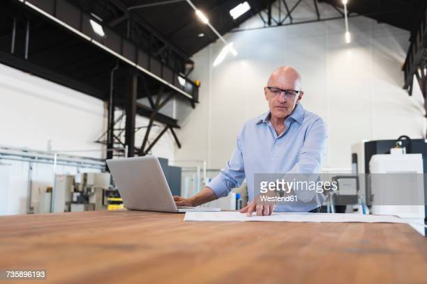 Man with laptop looking at plan on table in factory