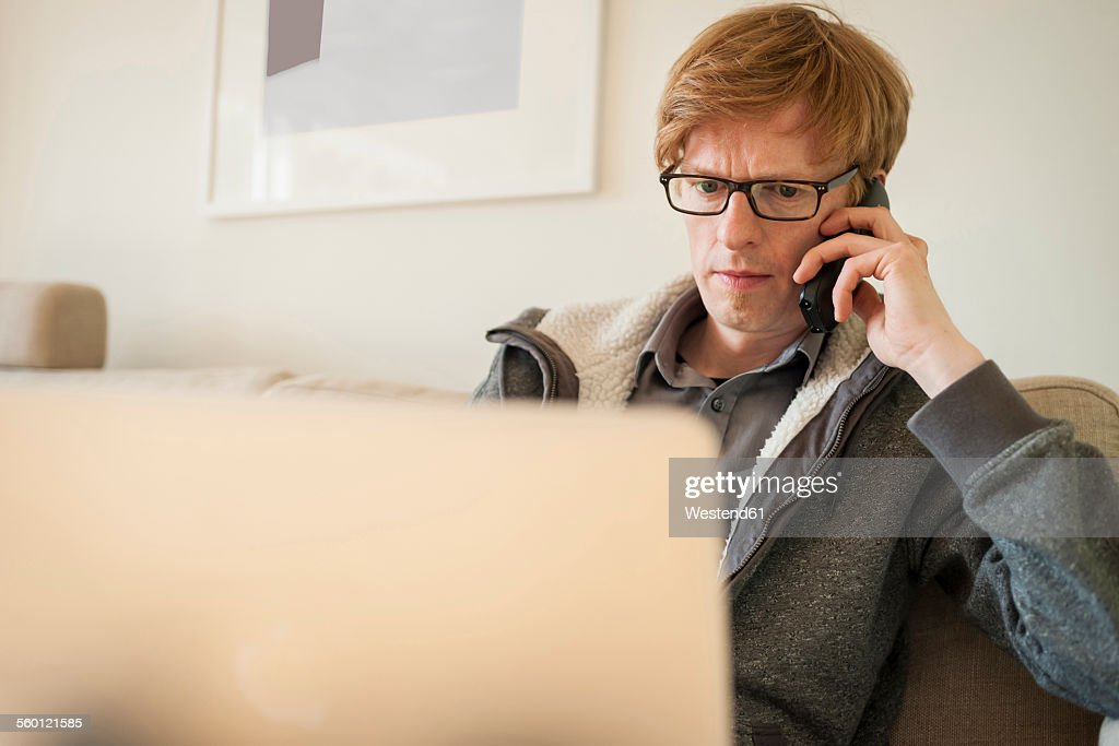 Man with laptop on the phone