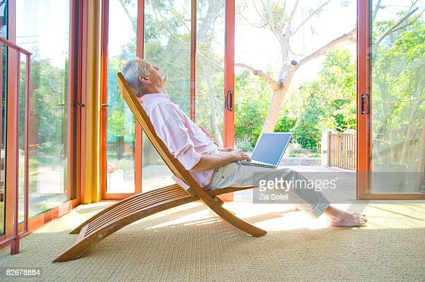 man with laptop relaxing on chair