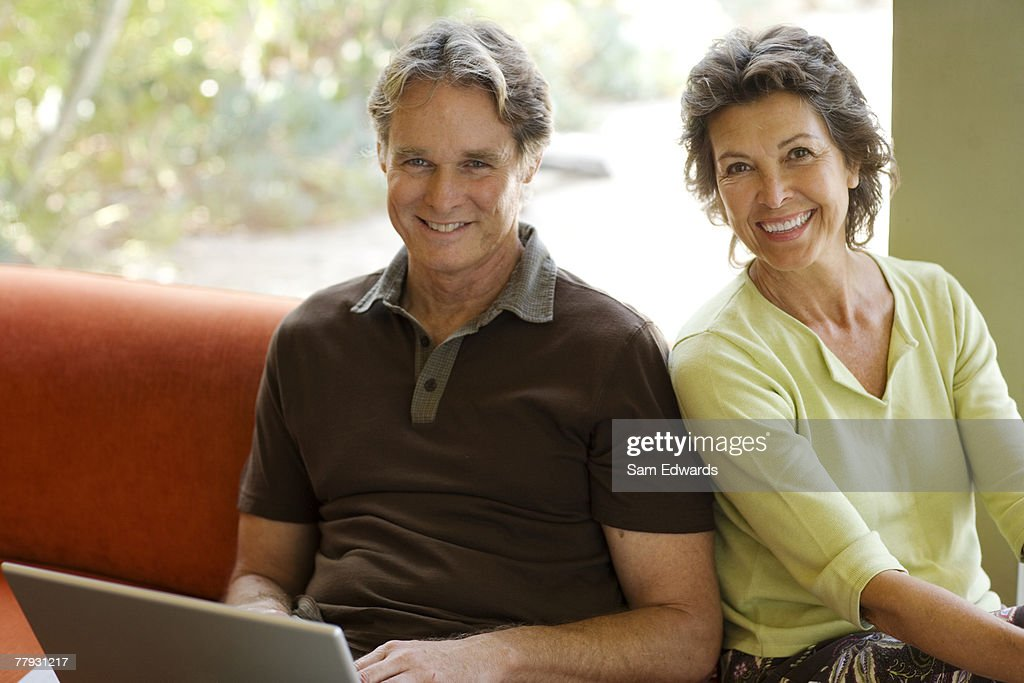 Man with laptop sitting beside woman in modern home : Stock Photo