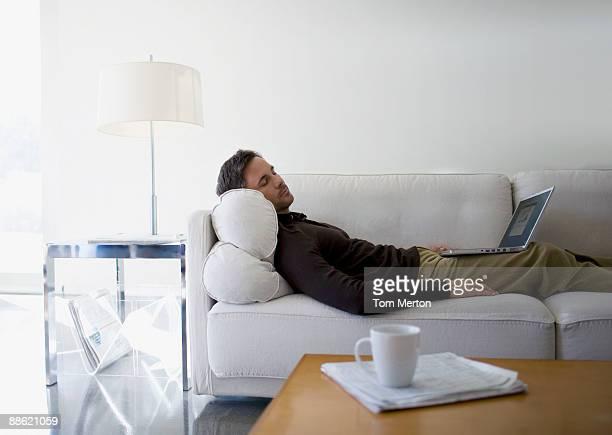Homme avec ordinateur portable sur canapé, chambre à coucher