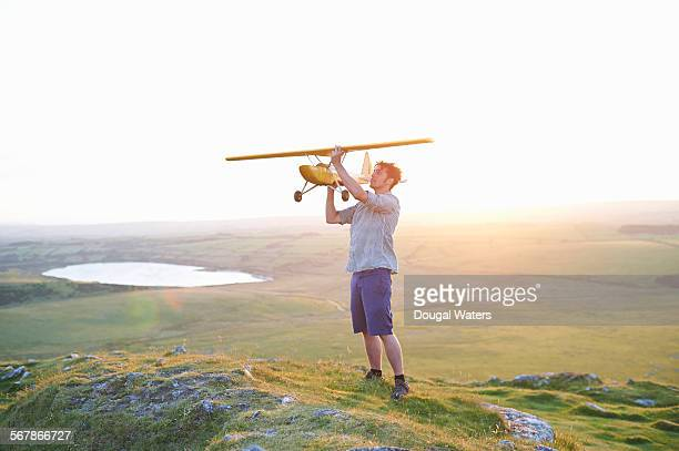 Man with large model airplane on hilltop.