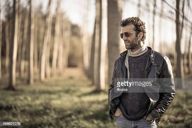 Mann mit Lederjacke und jeans in der Natur im Herbst