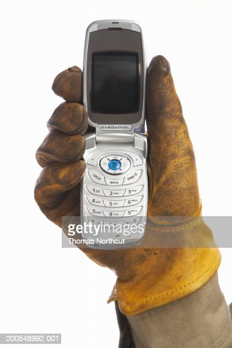 Man with leather work glove holding cell phone, close-up of hand