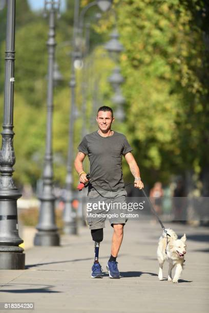Man with leg prosthesis walking with a dog