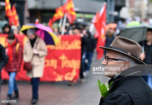 A man with lily of the valley in the buttonholes attends the traditional May Day rally in Strasbourg eastern France on May 1 2017 / AFP PHOTO /...