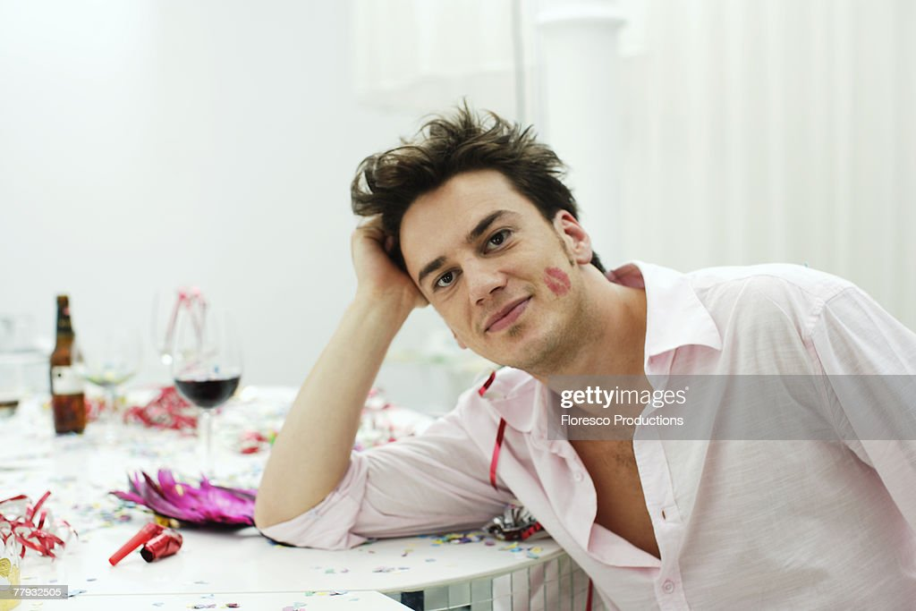 Man with lipstick on cheek leaning on table : Stock Photo