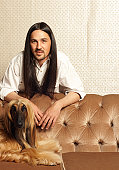 Man with long dark hair standing by Afghan hound lying on sofa, portrait
