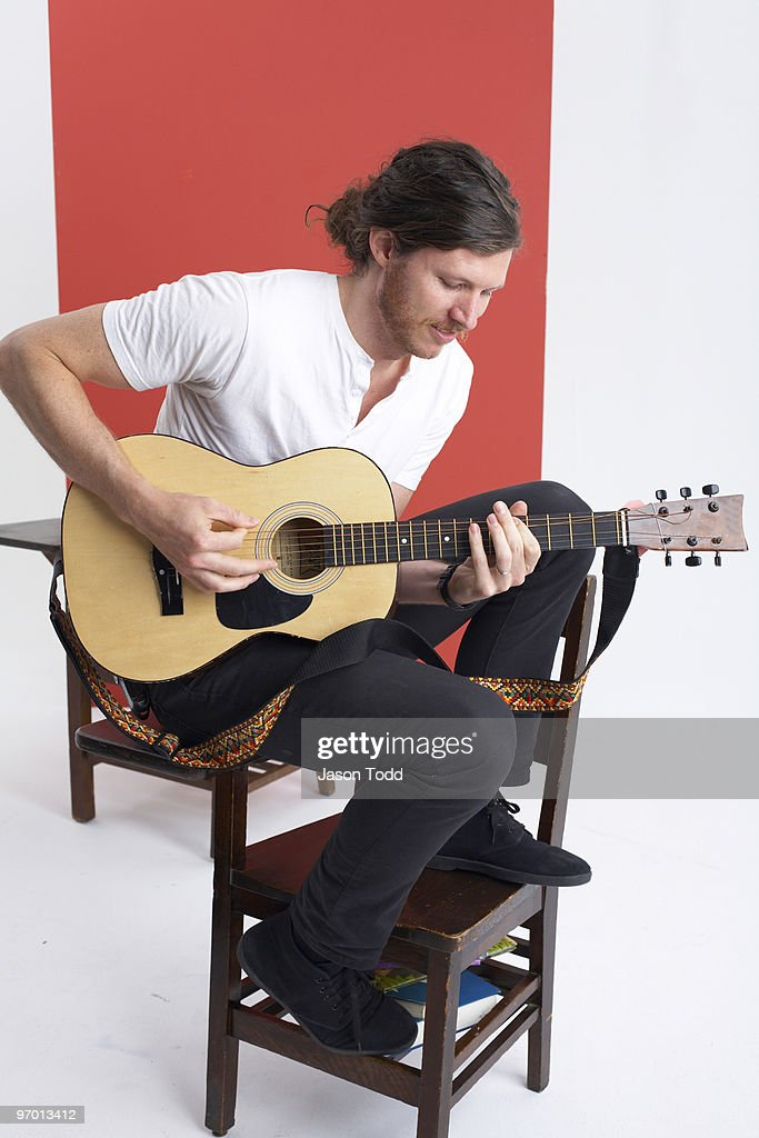 man with long hair playing guitar on school desk : Foto de stock