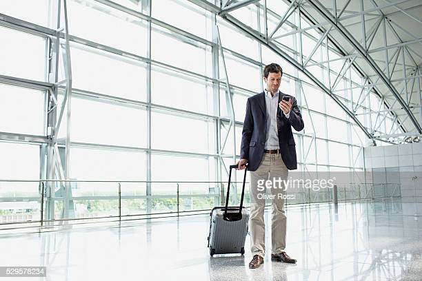 Man with luggage in airport lobby