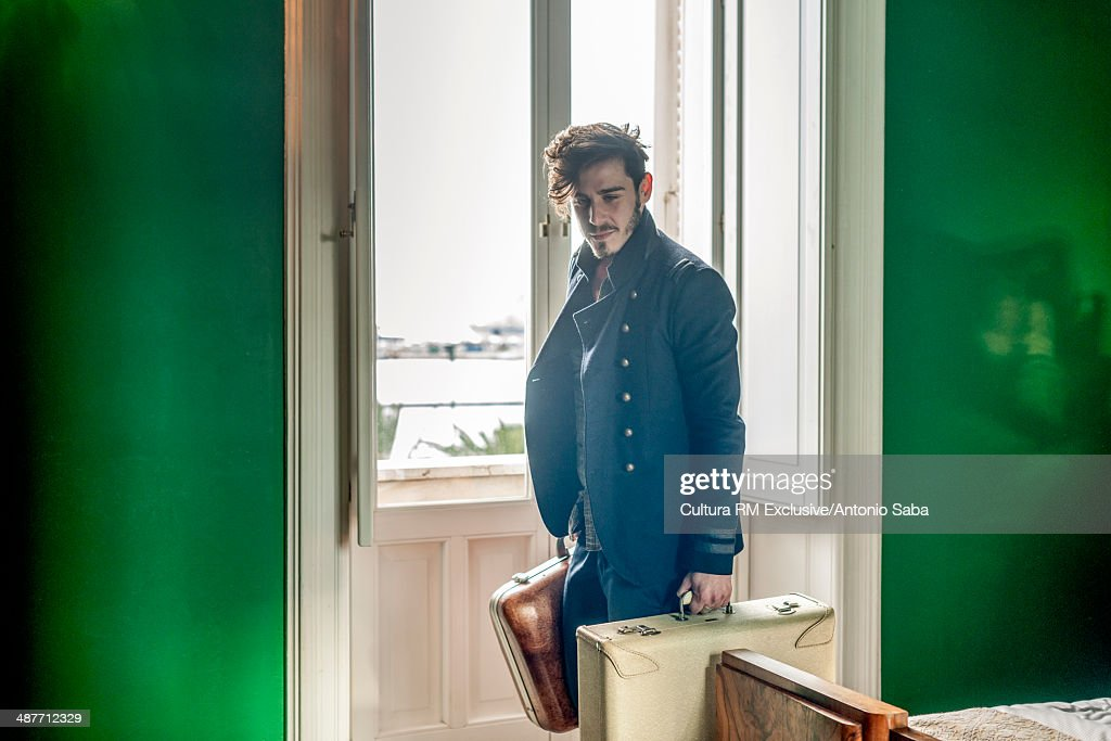Man with luggage in bedroom : Stock Photo