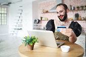 Man with make-up using laptop and credit card