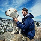 Man with mastiff sitting on rock, Portrait