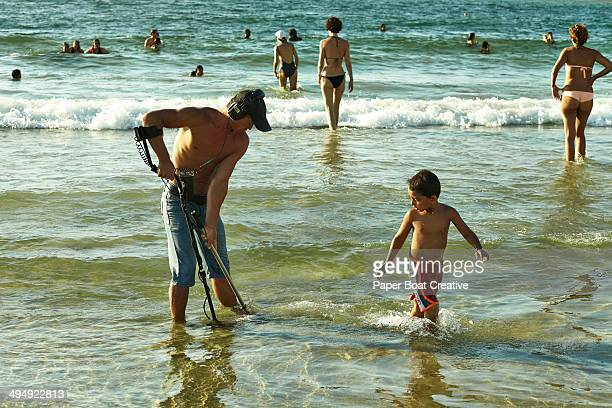 Man with metal detector by a beach in Israel