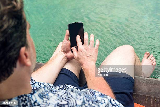 Man with Mobile Phone at Pool on Tropical Vacation Asia