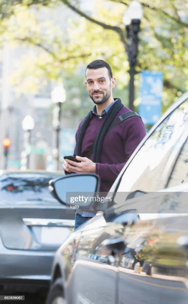 Man with mobile phone on city street, waiting for car : Stock Photo