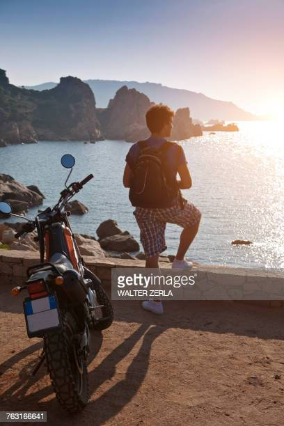 Man with motorbike looking away at view of sunset over sea, Olbia, Sardinia, Italy