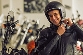 Attractive young blond man in black leather jacket is looking at camera, adjusting his helmet and smiling while standing in a motorbike salon