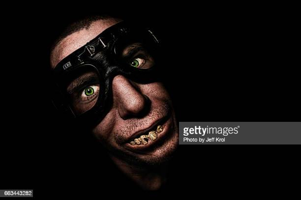 Man with motorcycle goggles or glasses, with funny fake teeth, smiling