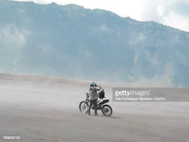 Man With Motorcycle On Dirt Road Against Mountain