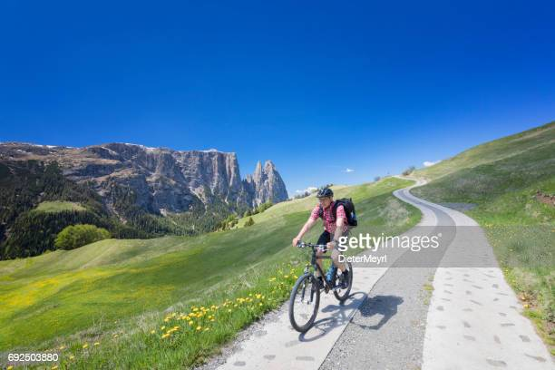 Man with Mountain bike at Alpe di Siusi - Mount Schlern in background