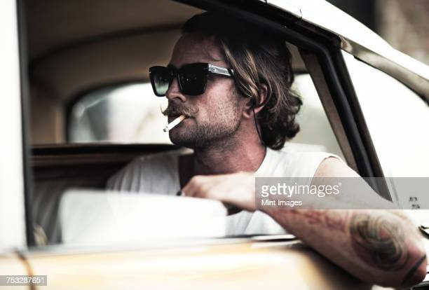 Man with moustache sitting in car, wearing sunglasses, smoking a cigarette, tattooed arm leaning out of window.