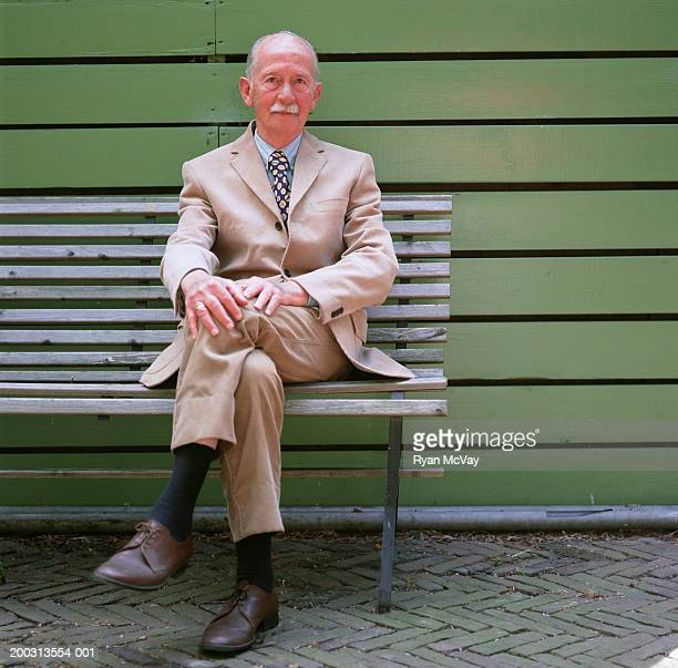 Man with moustache sitting on bench, outdoors, portrait