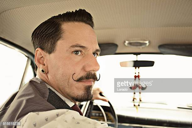 Man with moustaches driving  car