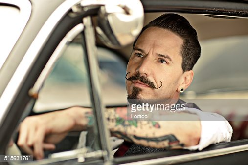 Man with moustaches sitting  in car