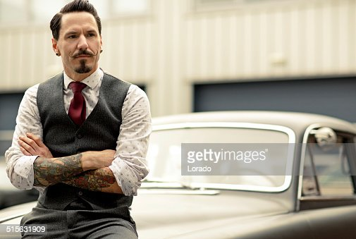 Man with moustaches sitting on retro  car