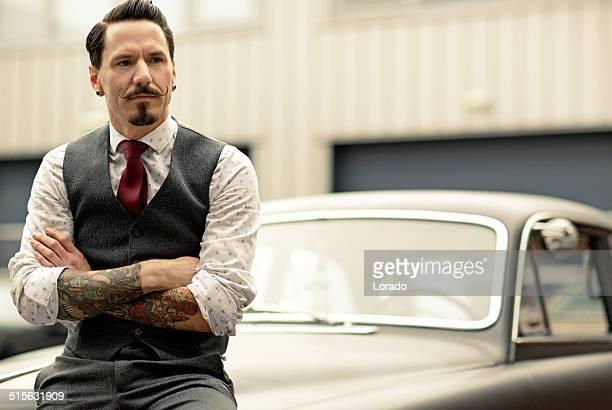 Homme avec barbe assis sur une voiture rétro