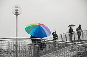 Man With Multi Colored Umbrella Standing On Bridge Against Clear Sky