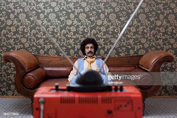 Man With Mustache Sitting On Sofa And Watching Television
