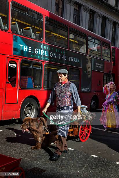 Man with Newfoundland dog pulling a cart of offerings along Cheapside to the Pearly Kings and Queens Harvest Festival In St Mary Le Bow Church The...