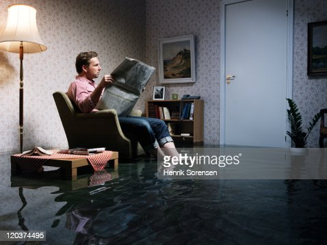 man with newspaper flooded room : Stock Photo