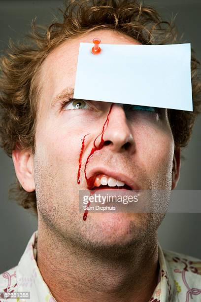 Man with note tacked to forehead, blood running down face