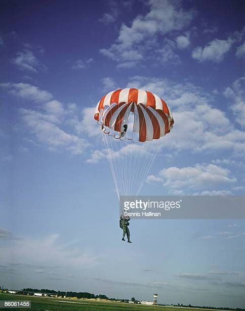 Man with open parachute about to land