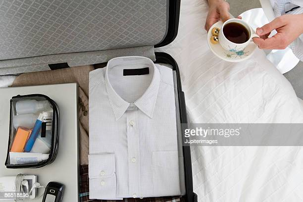 Man with open suitcase and coffee