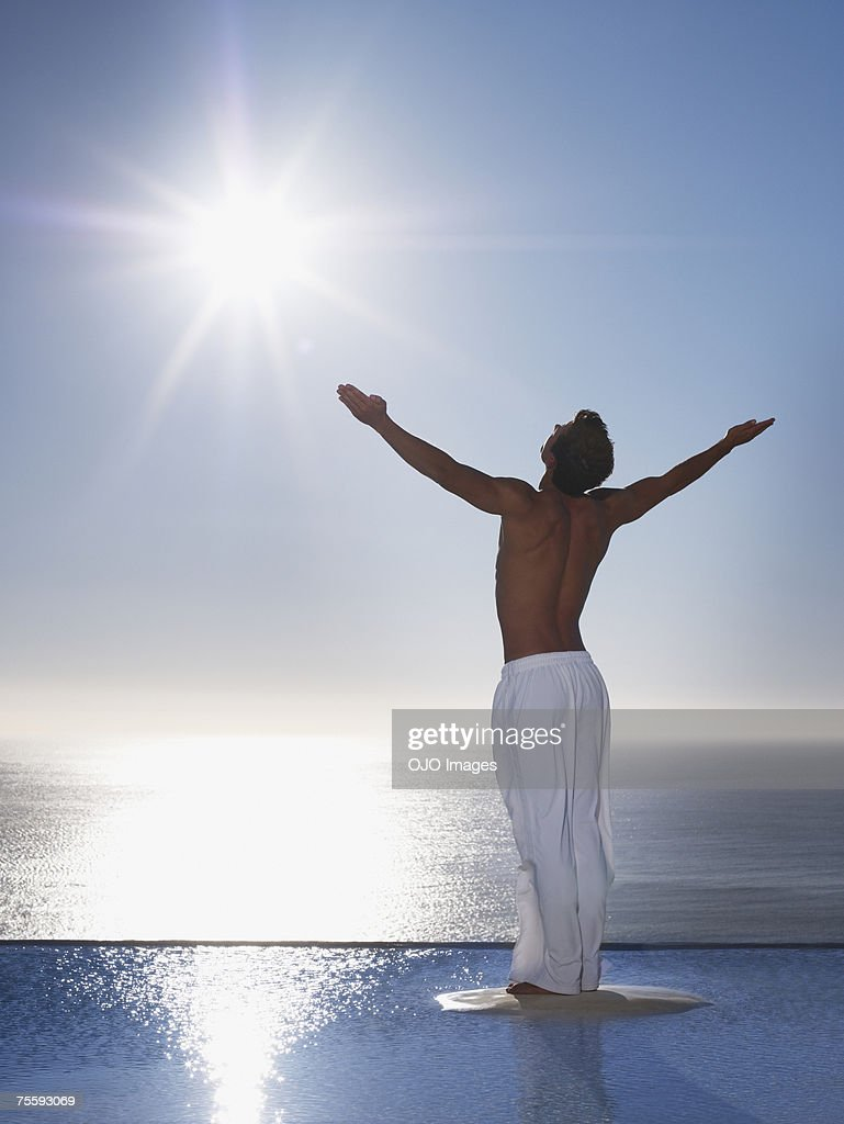 Man with outstretched arms by tranquil waters : Stock Photo
