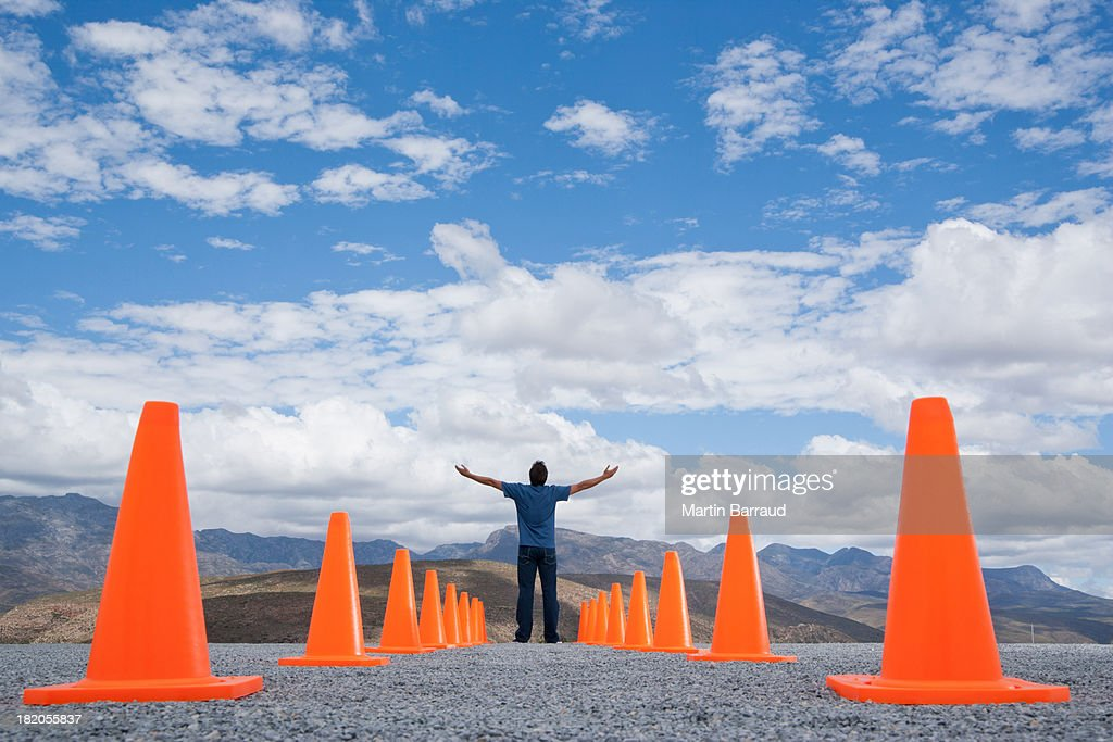 Man with outstretched arms standing in-between two rows of safety cones