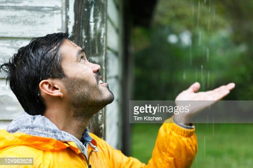 Man with outstretched hand near shed in rainstorm : Stock Photo