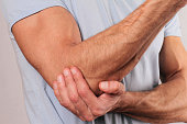 Man With Pain In Elbow. Pain relief concept
